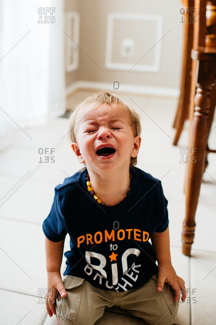 Young boy sitting on a kitchen floor throwing a tantrum