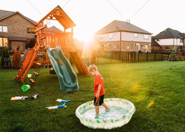Boy playing in child's pool in his backyard