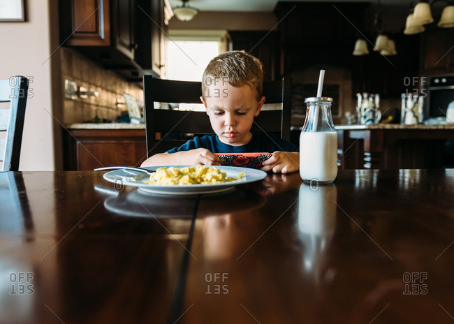 Little boy playing games on a smartphone during breakfast