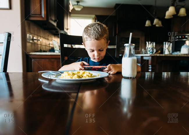 Little boy playing on a smartphone during breakfast
