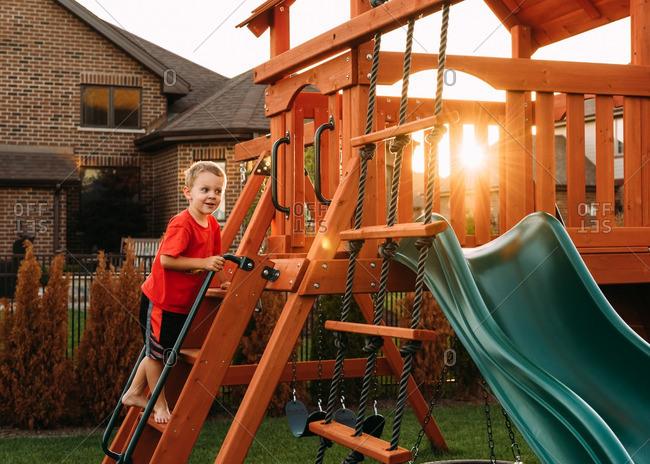 Boy climbing up a wooden play set in his backyard