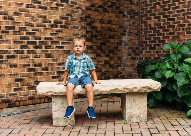 Boy sitting on stone bench by brick wall