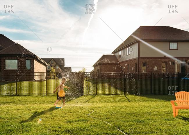 Boy running through a sprinkler in his backyard