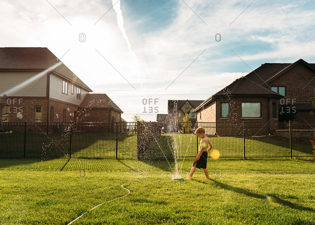 Boy playing in a sprinkler in his backyard