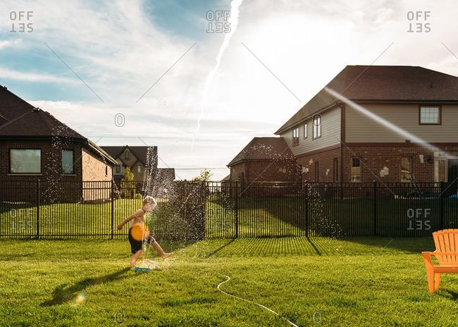 Boy splashing in a sprinkler in his backyard