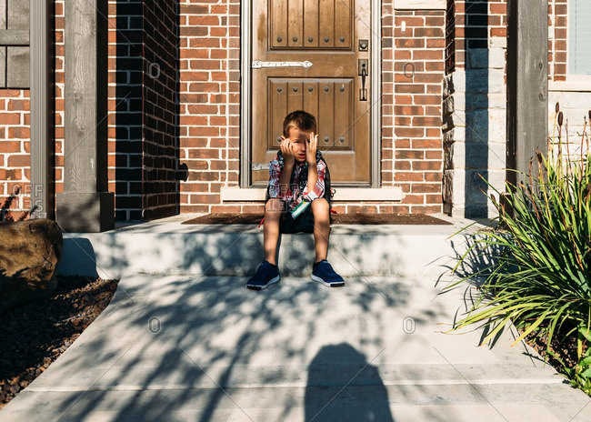 Boy sitting on front porch before his first day of school