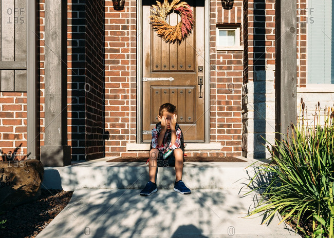Boy blocking sun from face on first day of school