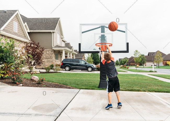 Little boy playing basketball in his driveway