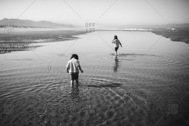 Two little girls playing in a lake