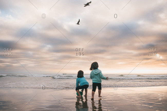 Two sisters playing in the ocean tide