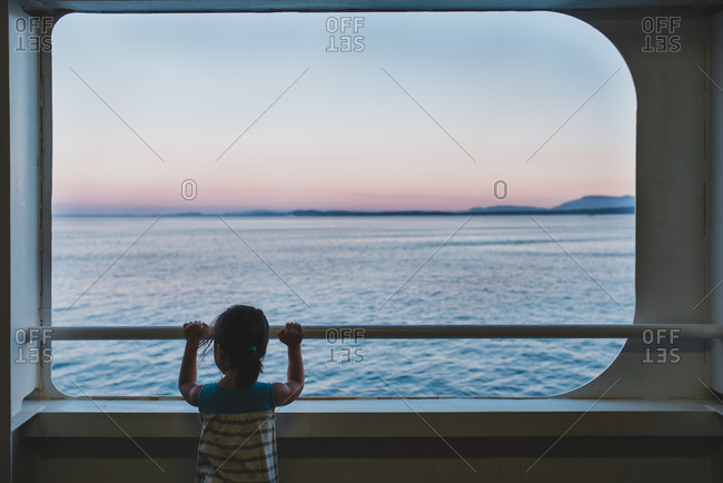 Little girl looking over ship railing at the sea