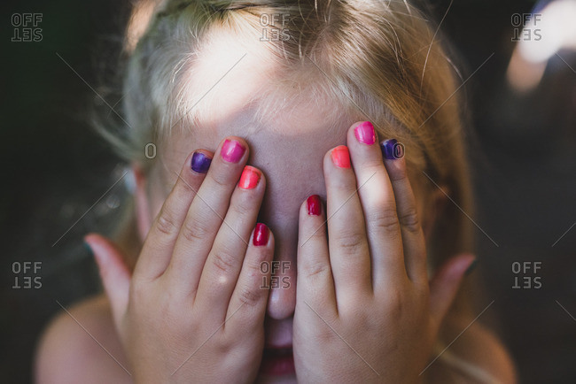 Little girl covering her face with colorful fingernails