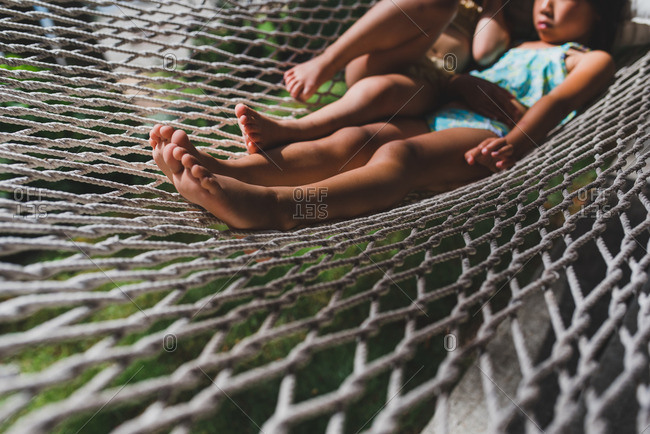 Two little girls swinging together in a hammock