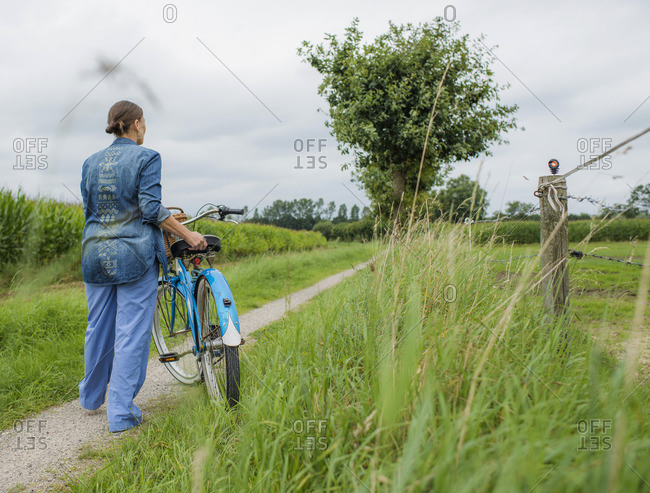 Rear view of woman standing with bicycle on rural road