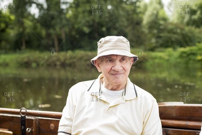 Senior man with cap sitting in boat during summer, Berkelzomp, Lochem, Achterhoek, Gelderland, The Netherlands