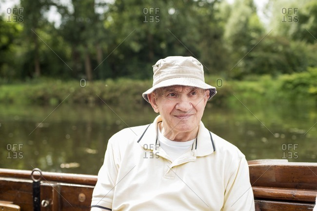 Senior man with cap sitting in boat during summer, Berkelzomp, Lochem, Achterhoek, Gelderland, The Netherlands