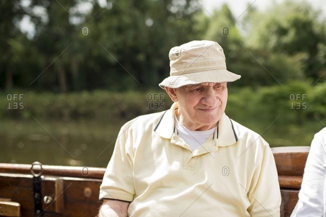 Senior man with cap riding on a boat during summer, Berkelzomp, Lochem, Achterhoek, Gelderland, The Netherlands