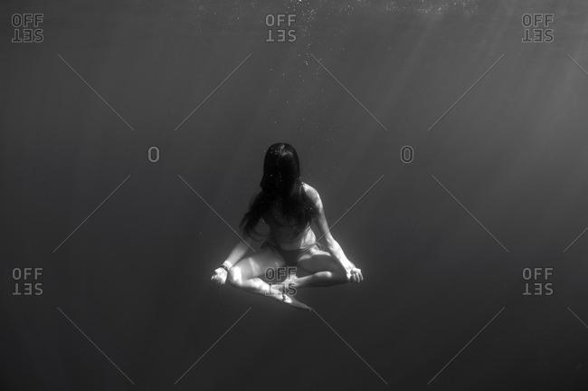 Woman meditating cross-legged underwater