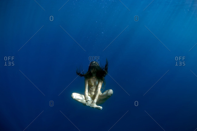 Woman sitting cross-legged underwater