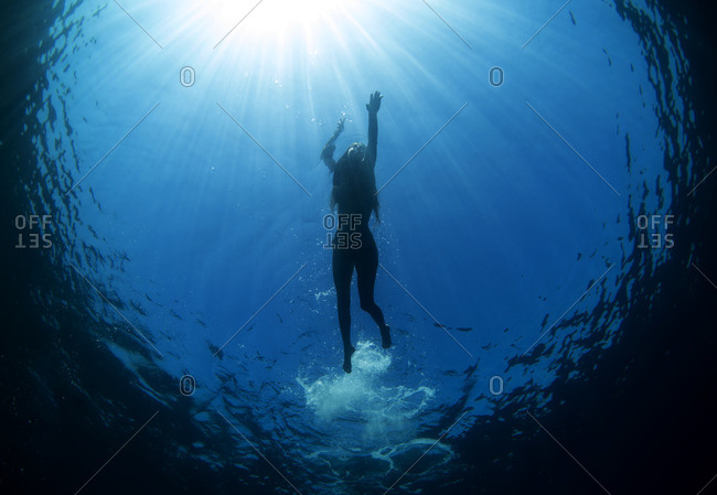 Underwater silhouette of woman swimming in the ocean's blue water