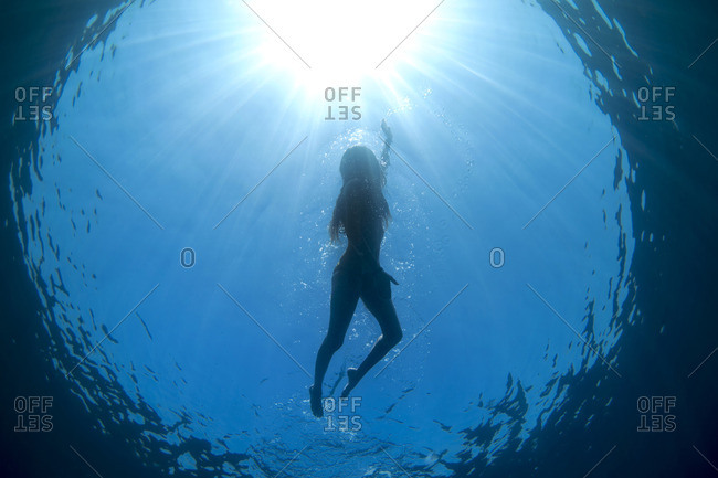 Underwater view of woman swimming in the ocean's blue water