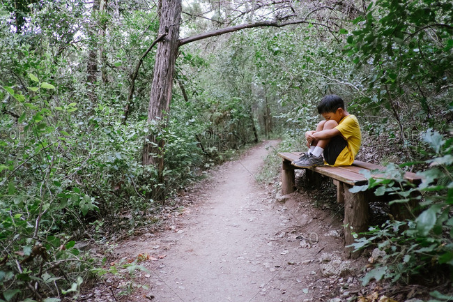 Boy sitting on a bench in the woods with his head resting on his knees