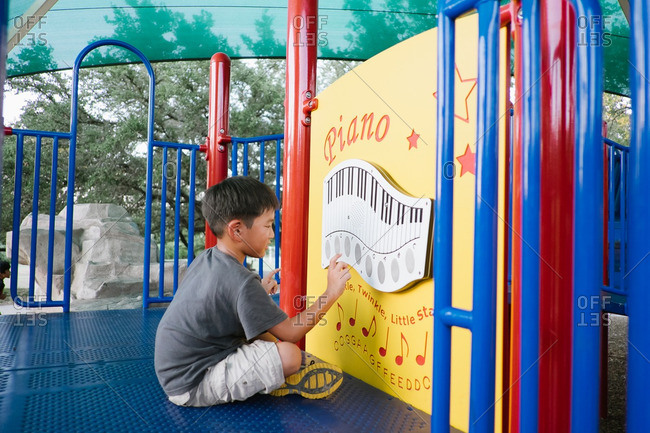Boy playing a piano game on playground equipment