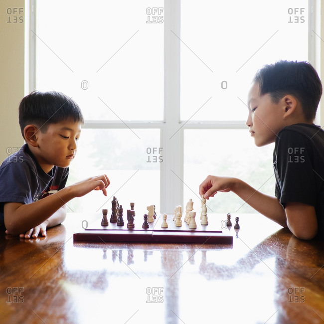 Two brothers playing chess at a wooden table