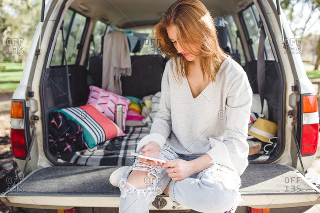 Young woman sitting on the tailgate of an SUV checking her phone