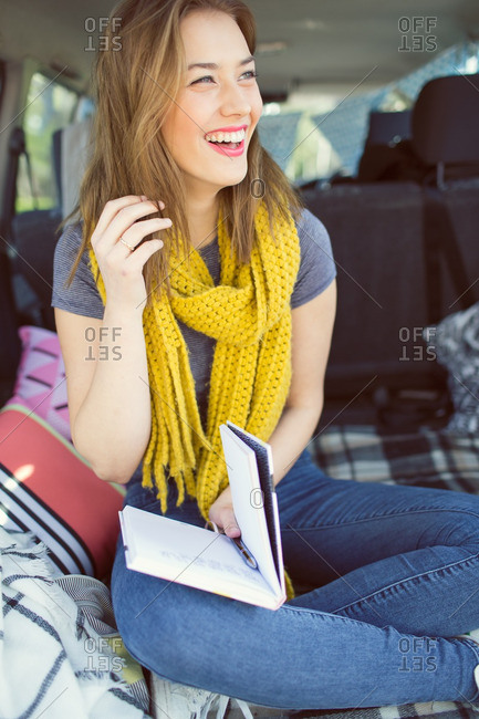 Young woman sitting in the back of an SUV holding a book