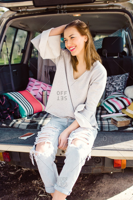 Young woman sitting on an SUV tailgate smiling