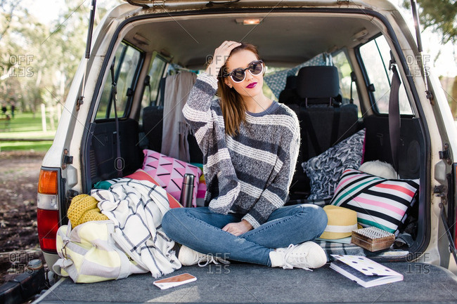 Young woman hanging out on pillows in the back of an SUV