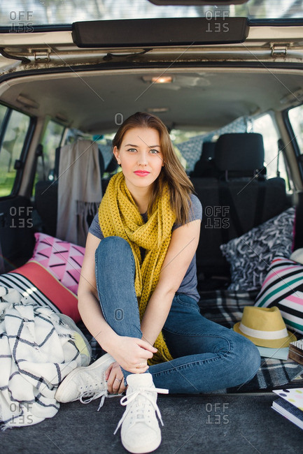 Young woman sitting on pillows in the back of an SUV