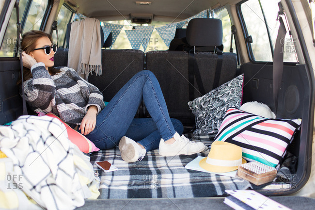 Young woman relaxing on pillows in the back of an SUV