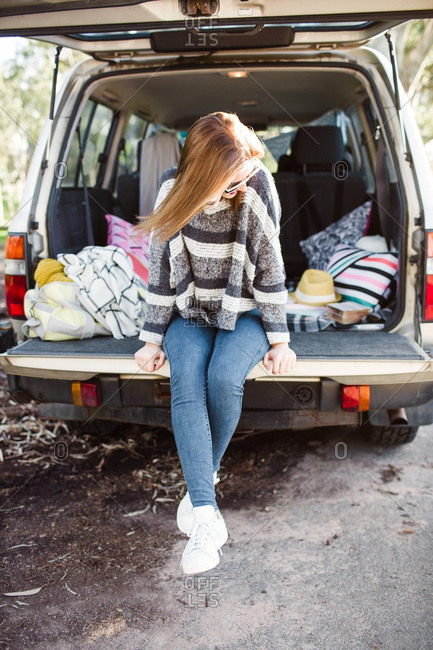Young woman sitting on an SUV tailgate dangling her legs