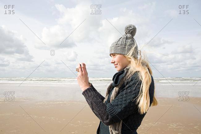 Woman by the sea with camera
