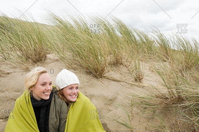 Women sharing a blanket on dune