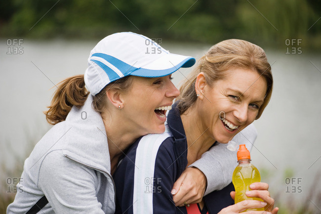 Two mature female friends laughing