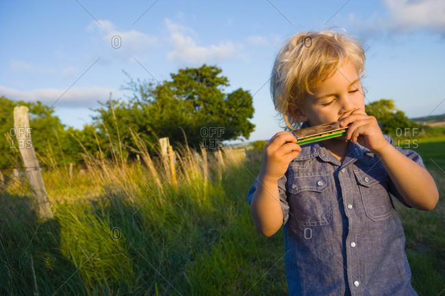 A boy playing the harmonica