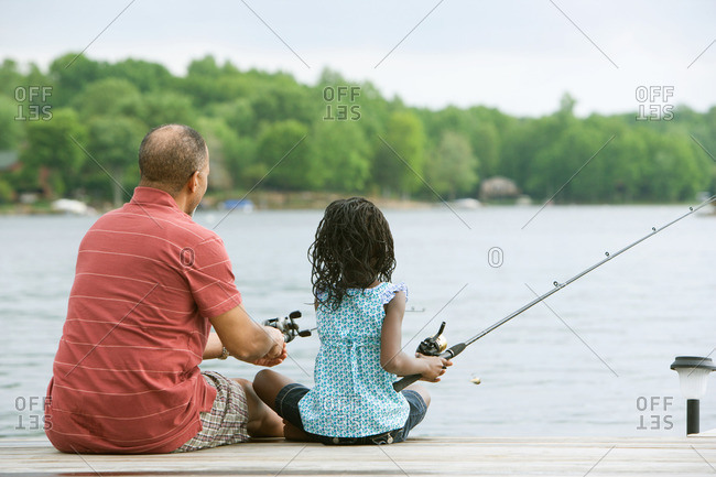 Rear view of a grandfather and granddaughter fishing