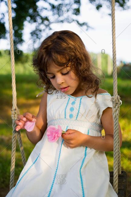 A girl picking petals off a flower