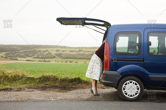 Woman looking in car boot
