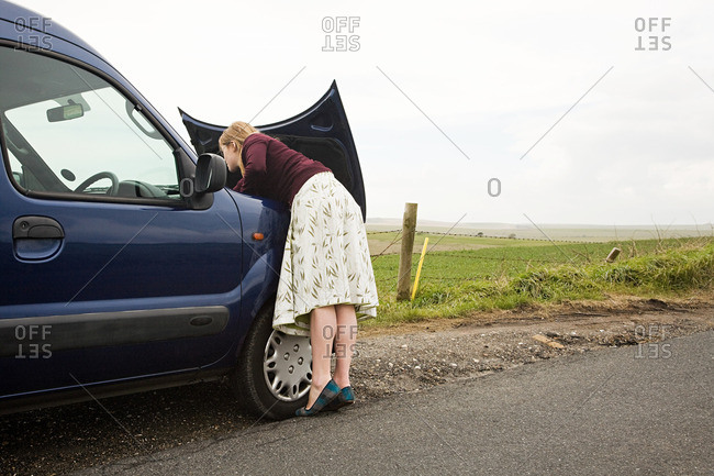 Woman looking under car bonnet