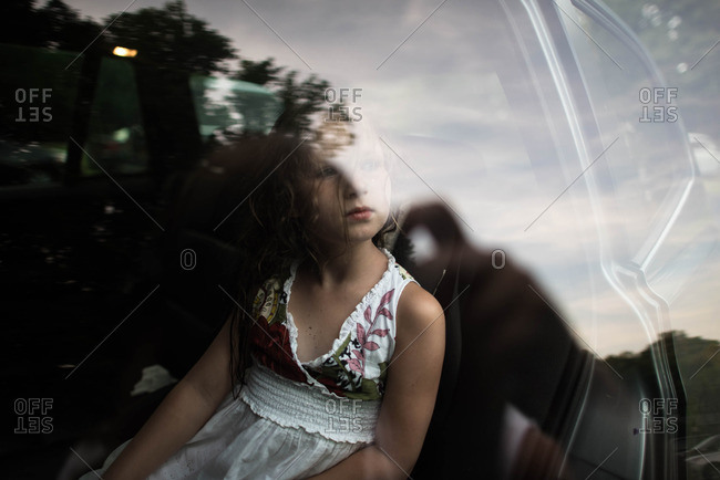 Little girl in a floral dress looking out a car window