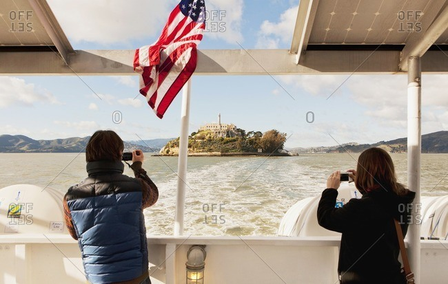 Alcatraz Island, San Francisco, California - January 11, 2013: People taking pictures of Alcatraz Island while riding the ferry back to San Francisco