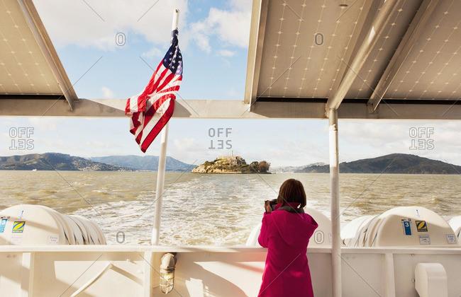 Alcatraz Island, San Francisco, California - January 11, 2013: Woman taking photo of Alcatraz Island from the ferry
