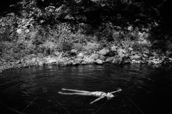 Girl floating on her back in a swimming hole