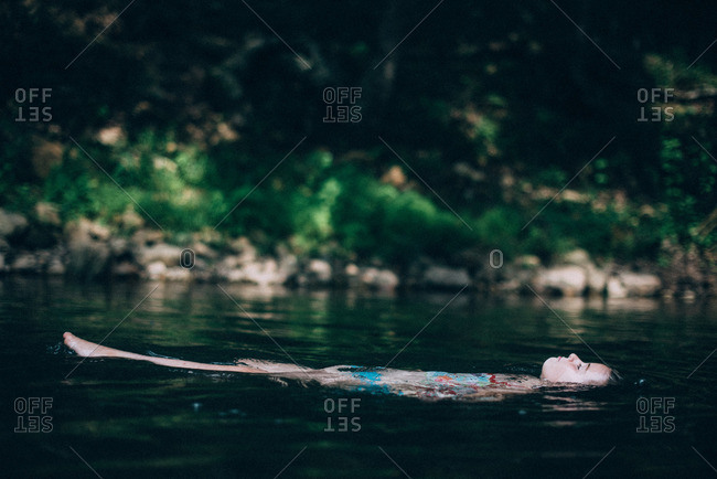 Girl floating calmly in a stream