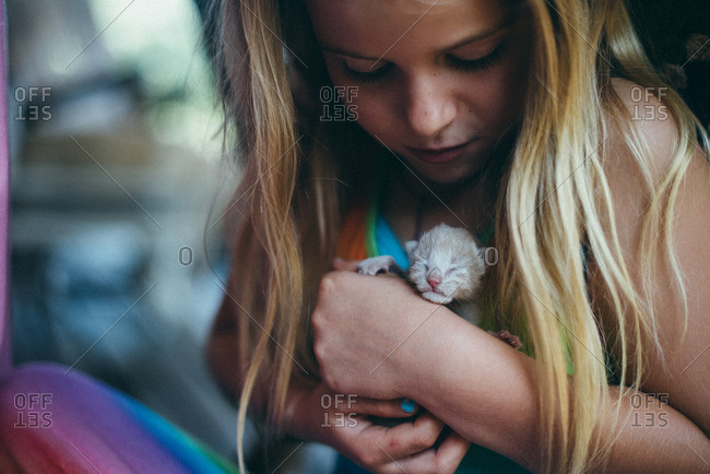 Girl holding a newborn kitten in her arms