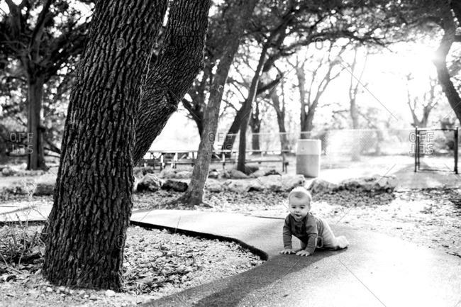Baby crawling on a wet sidewalk in a park